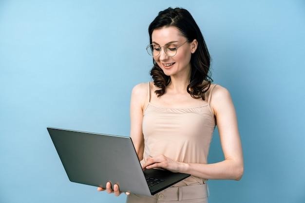 Donna di affari sorridente in vetri che lavorano al computer portatile.