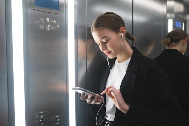 La donna di affari sorridente sta usando il suo smartphone con le cuffie nell'ascensore.