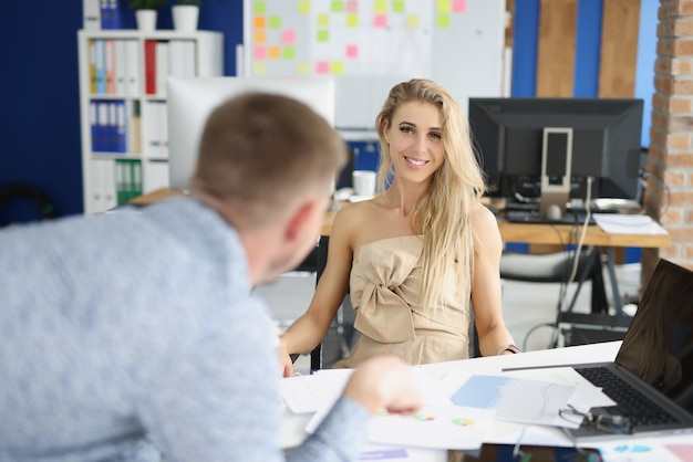 La donna di affari sorridente ascolta il rapporto di affari dal collega