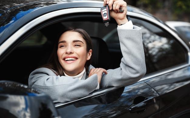Sorridente imprenditrice guardando fuori dalla finestra e mostrando le chiavi della macchina