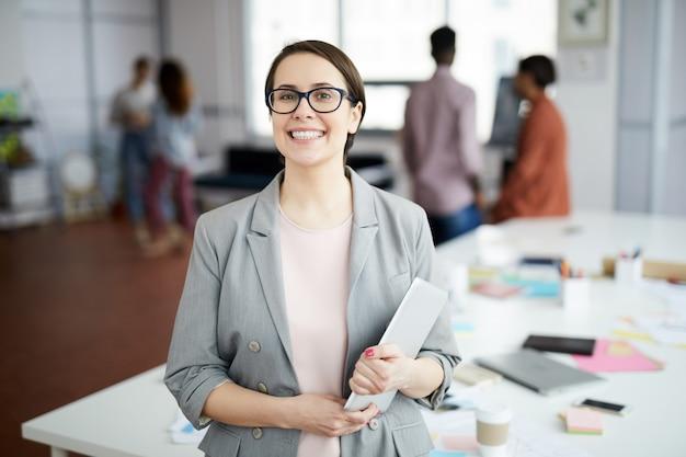Donna di affari sorridente che posa nell'ufficio