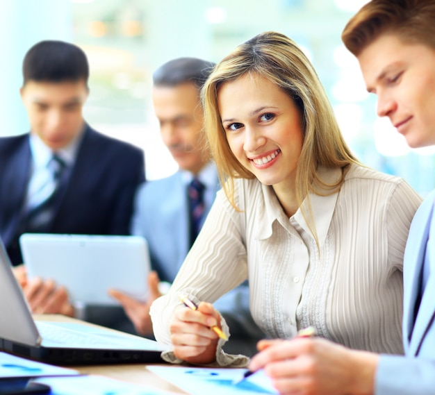 Sorridente imprenditrice in posa mentre i colleghi parlano insieme in ufficio luminoso