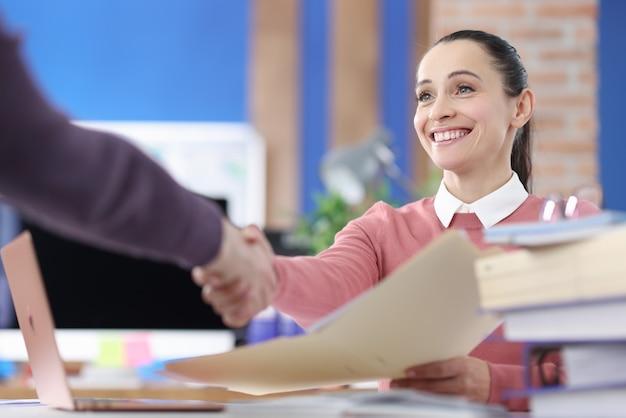 Sorridente imprenditrice stringe la mano al partner commerciale. accordo di affari e concetto di accordi di firma