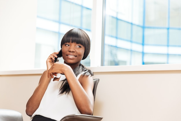 Donna d'affari sorridente che parla al telefono in ufficio e distoglie lo sguardo