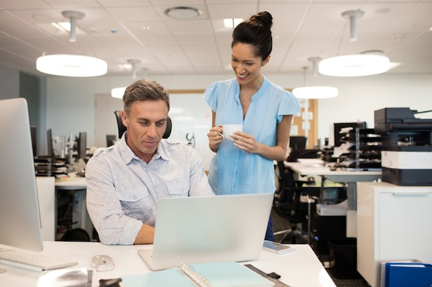 Sorridente imprenditrice parlando con un collega di sesso maschile in ufficio