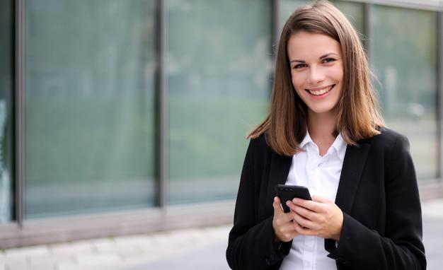 Donna di affari sorridente che per mezzo di uno smartphone all'aperto
