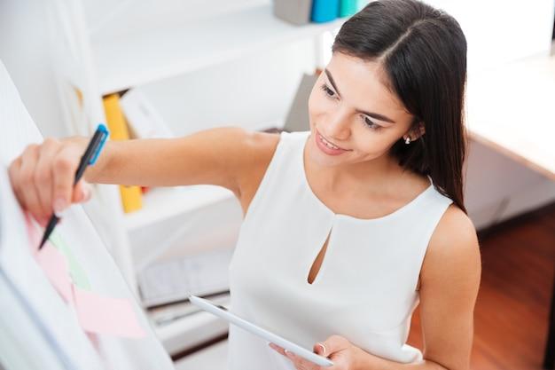 Donna d'affari sorridente che scrive sulla lavagna in ufficio