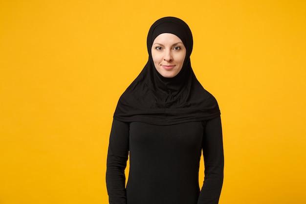 La giovane donna musulmana araba calma sorridente in hijab copre i suoi vestiti neri dei capelli isolati sulla parete gialla, ritratto. concetto di stile di vita religioso della gente. mock up copia spazio