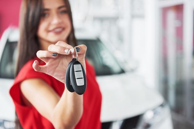 Rappresentante di automobile sorridente che consegna le vostre nuove chiavi dell'automobile, gestione commerciale e concetto di vendite. ragazza felice l'acquirente