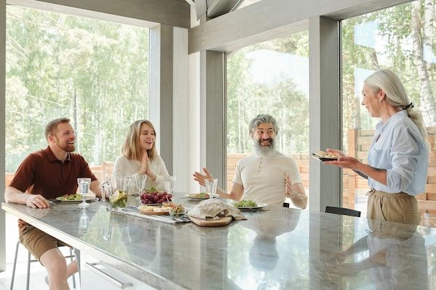 Madre senior attenta sorridente che dà gli antipasti alla famiglia mentre cenano insieme nella sala da pranzo