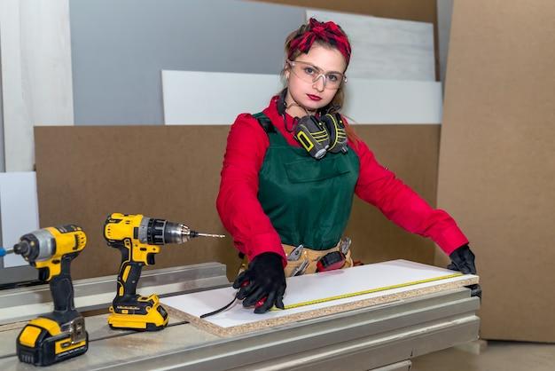 Falegname sorridente che misura la plancia di legno dal metro
