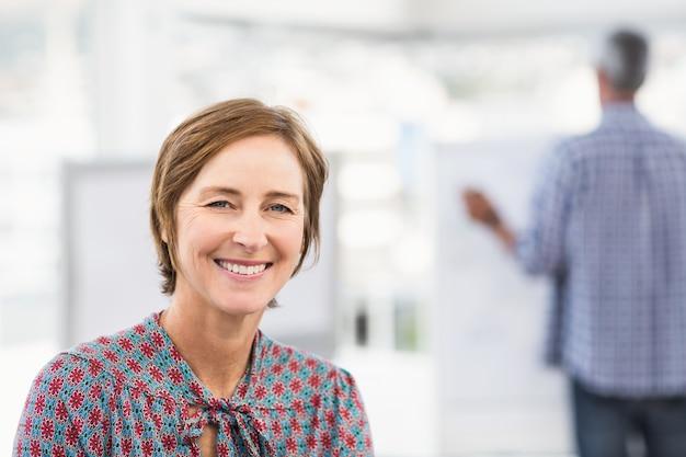 Donna di affari casuale sorridente davanti al collega