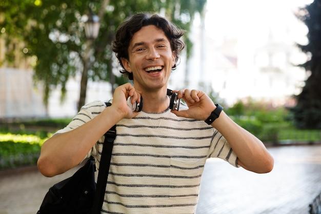 Sorridente uomo casual che trasporta zaino in strada della città