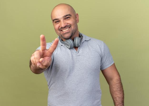 Sorridente casual uomo di mezza età che indossa le cuffie intorno al collo facendo segno di pace isolato sul muro verde oliva
