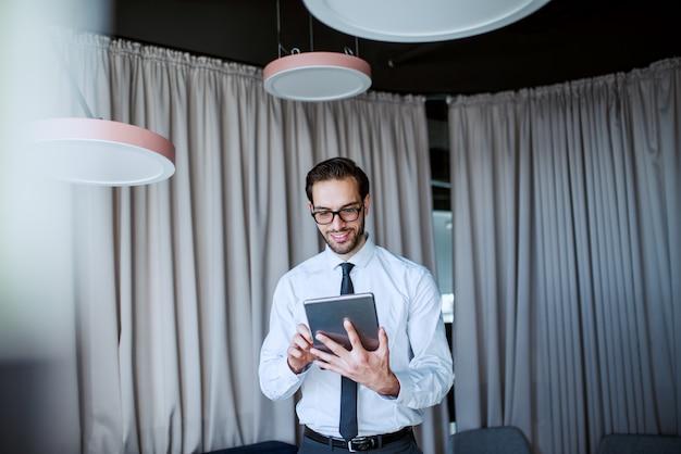 Sorridente uomo d'affari caucasico barbuto in camicia e cravatta e con gli occhiali in piedi in ufficio moderno e utilizzando tablet.