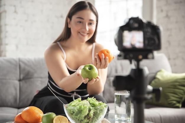 Sorridente. blogger caucasica, la donna fa vlog come fare una dieta e perdere peso, essere positiva per il corpo, mangiare sano. usando la videocamera che registra la sua preparazione di macedonia di frutta.