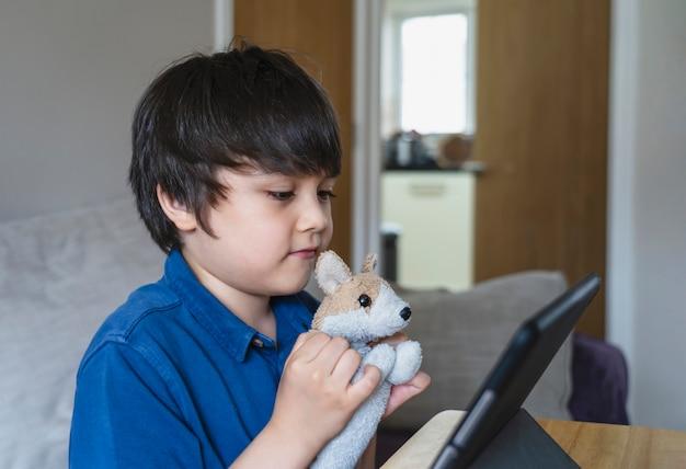 Il ragazzo caucasico sorridente ha videochiamata classe distante con l'insegnante sul tablet, il bambino felice che mostra il suo giocattolo agli amici tavoletta digitale, homeschooling, concetto di educazione sociale a distanza