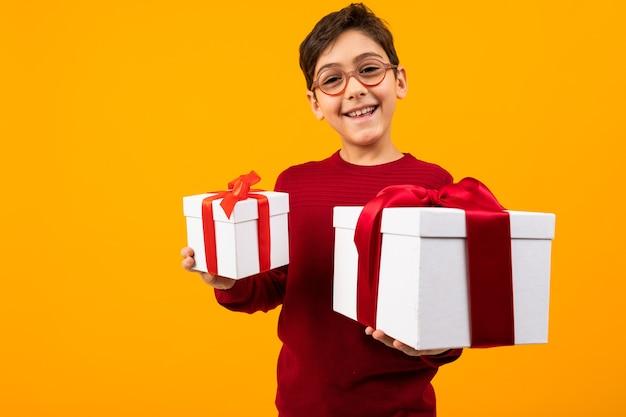 Ragazzo caucasico sorridente in un maglione rosso con due scatole di un regalo per il giorno di san valentino su uno sfondo giallo.