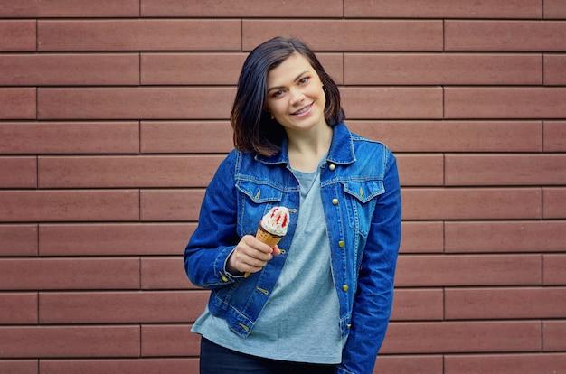 Sorridente ragazza bruna caucasica che tiene in una mano gustoso gelato con marmellata di frutta rossa in una giacca di jeans blu vicino a un muro di mattoni marrone strutturato.