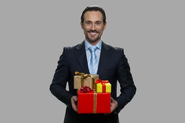 Sorridente imprenditore caucasico tenendo scatole regalo. ritratto dell'uomo bello in vestito di affari che tiene molti contenitori di regalo. festività natalizie.