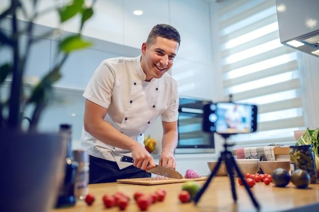 Cuoco unico caucasico sorridente in uniforme che sta nella cucina e che taglia cipolla mentre registrandosi per il blog