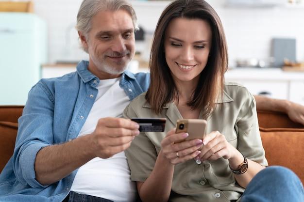 Sorridente coppia caucasica coinvolta nello shopping online, inserendo le informazioni di pagamento dalla carta di credito nell'applicazione mobile, soddisfatta del trasferimento di denaro rapido, concetto tecnologico moderno.