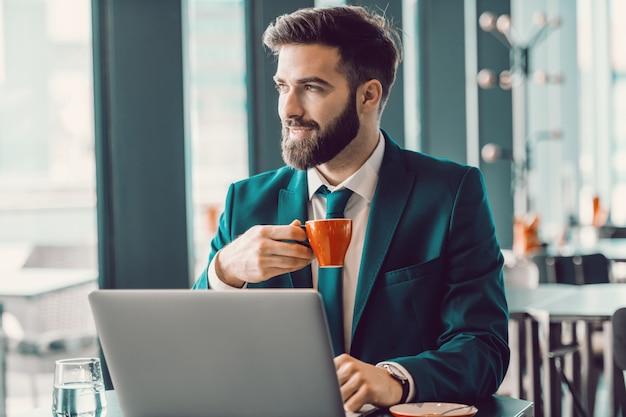 Caffè bevente sorridente dell'uomo d'affari elegante caucasico in caffè, facendo uso del computer portatile e guardando la finestra della depressione. spingiti, perché nessuno lo farà per te.