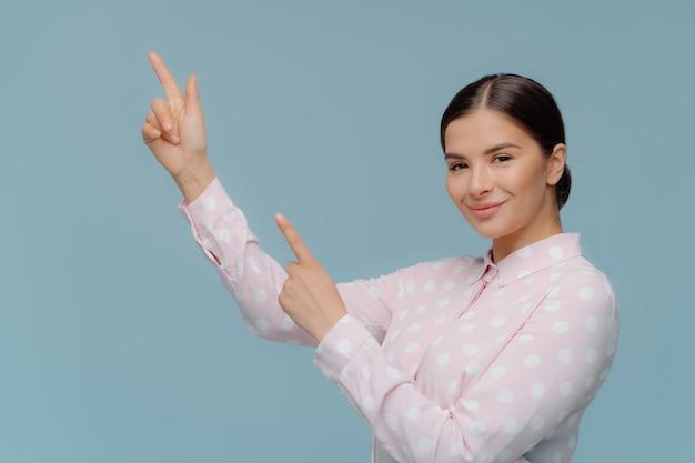 La femmina caucasica sorridente punta dritto verso l'alto, dimostra qualcosa nell'angolo in alto a sinistra