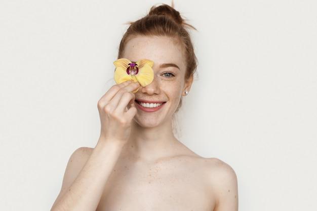 Sorridente signora caucasica con i capelli rossi e le lentiggini che coprono gli occhi con un fiore e in posa con le spalle nude