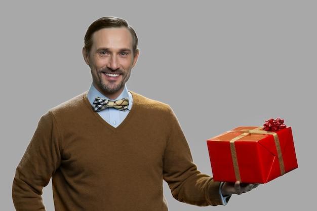 Contenitore di regalo caucasico sorridente della tenuta dell'uomo. spazio per il testo. celebrazione delle vacanze invernali.