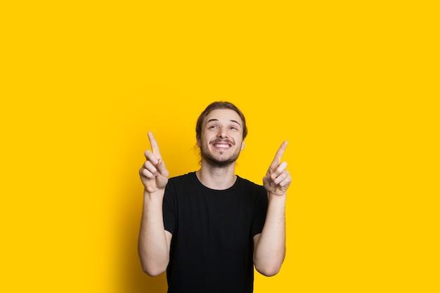 Sorridente uomo caucasico con barba e capelli lunghi è rivolto verso lo spazio libero giallo sopra di lui