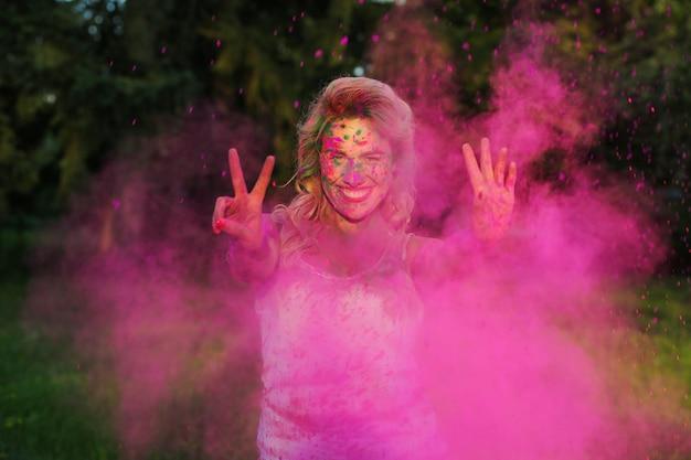 Sorridente modella caucasica con lunghi capelli ondulati in posa con schizzi di colore e mostrando gesto di pace