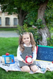 La studentessa caucasica sorridente con la grande sveglia rossa si rilassa sul prato inglese nel parco vicino alla scuola.