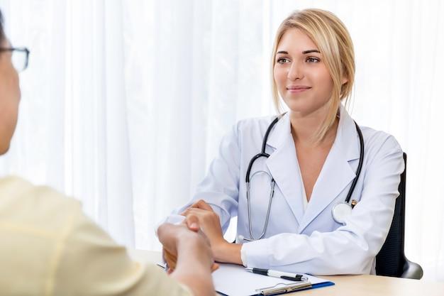 Medico sicuro sorridente della donna caucasica che stringe le mani con il paziente asiatico senior nella stanza di ospedale.