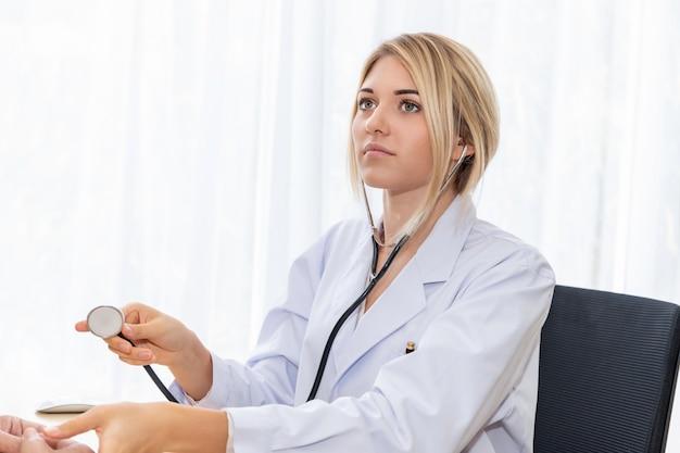 Medico caucasico sorridente della donna che posa e che indossa uno stetoscopio sulla stanza di ospedale.