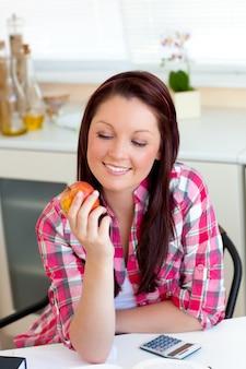 Donna caucasica sorridente che tiene una mela che si siede nella cucina