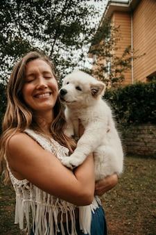 Sorridente donna caucasica tenendo il cucciolo samoiedo tra le braccia. concetto di animali e persone. concetto di simpatici animali.