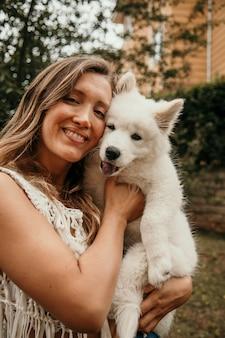 Sorridente donna caucasica tenendo il cucciolo samoiedo tra le braccia. concetto di animali e persone. animali carini