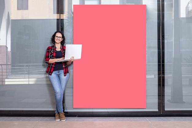 Sorridente donna caucasica in piedi mentre si utilizza un computer portatile accanto a una vetrina all'aperto