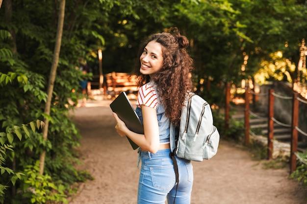 Sorridente donna indoeuropea indossando uno zaino, camminando attraverso un parco verde con laptop d'argento nelle mani