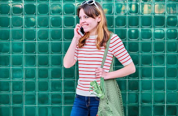 Sorridente ragazza giovane caucasica parlando al telefono cellulare con una borsa a rete sulla sua spalla con verdure su un muro verde in strada