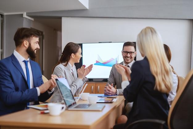 Ceo sorridente seduto nella sala del consiglio con la sua squadra. squadra che applaude a lui. una riunione è un evento in cui vengono conservati i minuti e le ore perse.