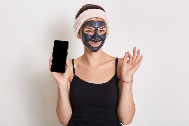 Sorridente donna affascinante indossa fascia per capelli e maglietta, tenendo il telefono con lo schermo vuoto, mostrando ok cantare le dita di spirito