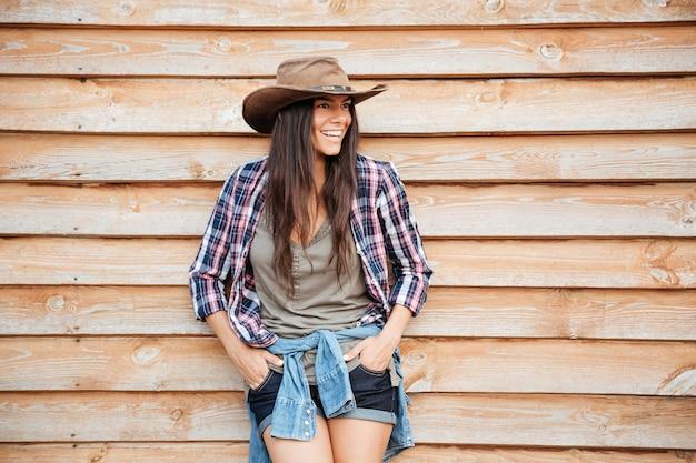 Sorridente affascinante giovane donna cowgirl in piedi su sfondo di legno