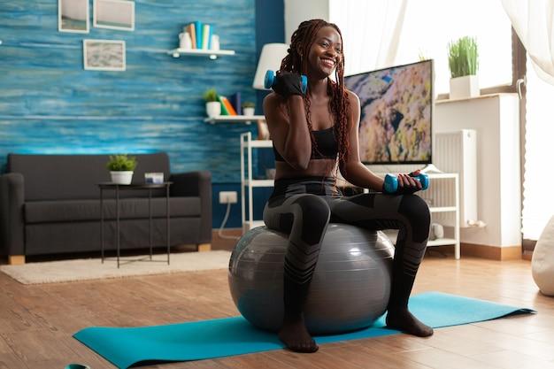 Sorridente donna africana allegra che flette il braccio allenando i bicipiti, usando manubri seduti sulla palla di stabilità che rende l'allenamento più difficile dopo il riscaldamento. forte persona atletica che fa sport a casa.