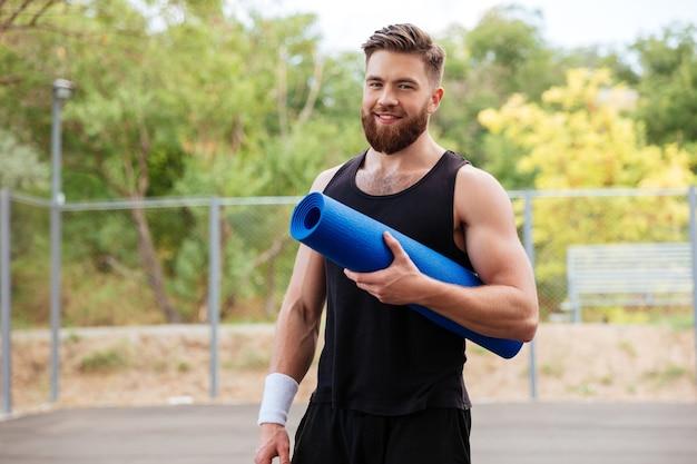 Sorridente allegro uomo fitness barbuto con tappetino da yoga in piedi all'aperto