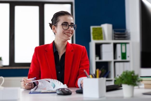 Sorridente imprenditrice allegra che fa scartoffie in ufficio aziendale sul posto di lavoro guardando computer d...