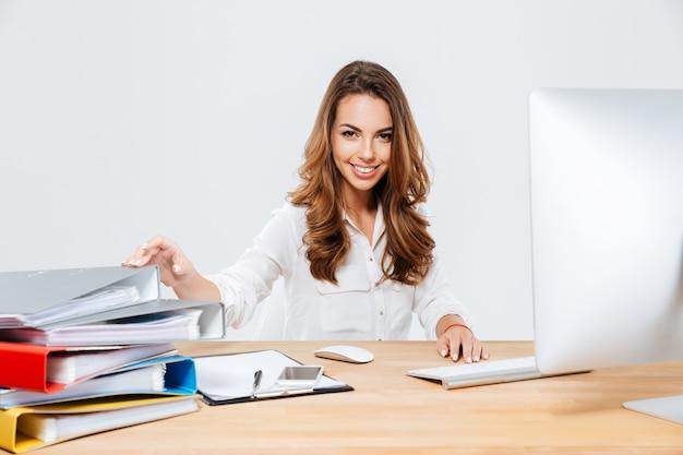 Sorridente imprenditrice allegra seduta al suo posto di lavoro isoltaed sullo sfondo bianco