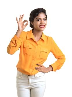 Sorridente ragazza allegra che mostra segno isolato sul muro bianco