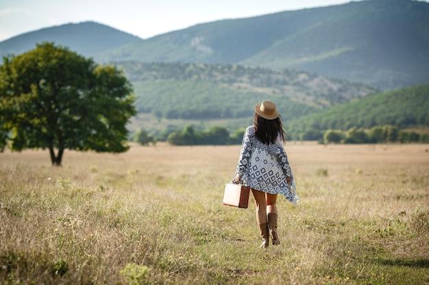 Sorridente ragazza allegra con i capelli ricci respira un seno pieno e gode della libertà, in piedi sul campo vicino al grande albero solo.